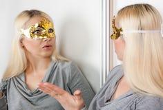 Die verdeckte Frau starrt entlang ihrer Reflexion im Spiegel an Stockbilder