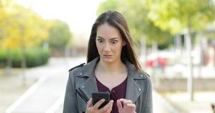 Die verdutzte Frau, die Telefon überprüft, betrachtet Kamera
