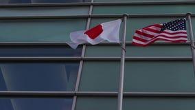 Die Vereinigten Staaten von Amerika und japanische Flaggen, die nebeneinander zusammen fliegen stock footage