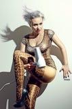 Die verrückte blonde Frau im Leoparden keucht mit hairdryer Stockfotos