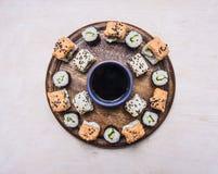 Die verschiedenen Arten von Sushi, ausgebreitet auf einem hölzernen runden Behälter, zeichneten mit einem Kreis um das asiatische Stockbilder