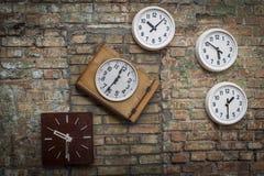Die verschiedenen in Form Retro- Uhren, die eine andere Zeit zeigen, hängend an einem Grau, verfielen Backsteinmauer Stockbild