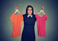 Die verwirrte Frau, die zwischen Kleidern wählt und kann Entscheidung nicht treffen stockbild