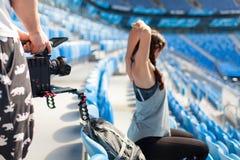Die videographer Trieb auf einer Berufskamera mögen ein sportliches Mädchenaufwärmen und sitzen im Stadion Stockbild