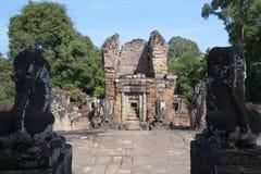 Die Wächterlöwestatuen, die in Richtung des Tors blicken, ragen an the10th-Jahrhundert Ost-Mebon-Tempel hoch Stockbild
