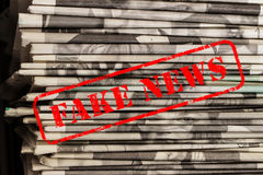 Die Wörter fälschen Nachrichten im roten Text auf Zeitungen stockfotos