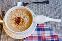 Die würzige Reismehlsuppe in der Schüssel auf Tischdecke Lizenzfreie Stockfotos