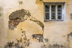 Die Wand eines alten Hauses mit einem Fenster Die Wandbedarfsreparatur, der eingestürzte Gips und die Maurerarbeit stockfoto