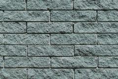 Die Wand und die Ziegelsteine sind grau oder grün Stockfoto