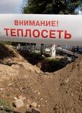 Die warnende Aufschrift ` Aufmerksamkeit zum Fernwärmenetz ` vor dem ausgegrabenen Graben stockbild