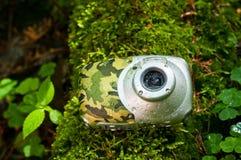 Die wasserdichte Kompaktkamera, die mit Wasser bedeckt wird, lässt das Lügen auf dem Waldboden fallen Lizenzfreie Stockfotografie