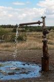 Die Wasserführung, die aus dem freigelegten Hahn heraus fließt Lizenzfreies Stockfoto