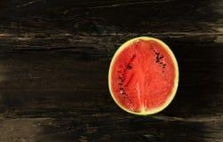 die Wassermelone ist Scheibe der Hälfte auf einem rustikalen hölzernen Hintergrund spindel Lizenzfreie Stockfotos