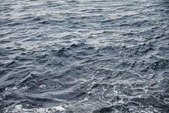 Die Wasseroberfläche ist mit weißem Schaum grau-blau Lizenzfreie Stockbilder