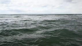 Die Wasseroberflächenaufregung am Ufer und am Himmel mit Wolken stock video footage