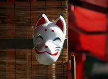 Die weiße Maske des Fuchses auf dem hölzernen Vorhang mit Sonnenlicht lizenzfreies stockfoto