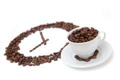 Die weiße Tasse Kaffee-Bohne vor Kornuhr Stockbilder