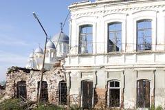 Die weiße Wand des zerstörten Gebäudes, durch deren Fenster die Hauben der orthodoxen Kirche sichtbar sind Stockfotos