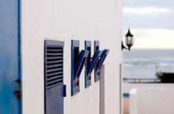 Die weiße Wand mit angelehnten Marinefenstern - Lanzarote, kanarische Inseln Lizenzfreies Stockfoto