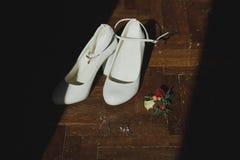 Die weißen ledernen hohen Absätze, die Schuhe heiraten, stehen auf dem dunklen Bretterboden Kleines Schmuckarmband und -ohrringe  lizenzfreies stockfoto