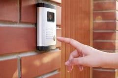 Die weibliche Hand drückt eine Knopftürklingel mit Wechselsprechanlage stockbild
