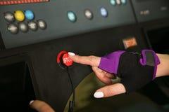 Die weibliche Hand drückt die STOPP-Taste auf der Tretmühle stockfoto