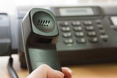 Die weibliche Hand hält ein Gefäß des schwarzen Telefons an Lizenzfreie Stockbilder