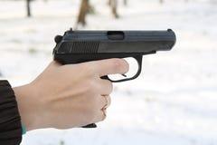 Die weibliche Hand hält eine Pistole an Stockfotografie