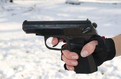 Die weibliche Hand hält eine Pistole an Stockbild