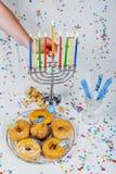 Die weibliche Hand, die Kerzen im menorah beleuchtet, diente für Chanukka Lizenzfreies Stockfoto