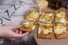 Die weibliche Hand nimmt eine Scheibe des Käses der Pizza vier mit Oregano und Olivenöl quattro fromaggi lizenzfreies stockfoto
