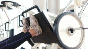 Die weiblichen Beine, die auf Maschine ausbilden, drücken Turnhalle ein stock video footage