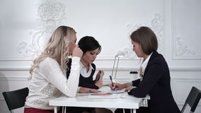 Die weiblichen Designer, die an einem Dokument und täuschen arbeiten dann, herum im Büro Timelaps stock footage