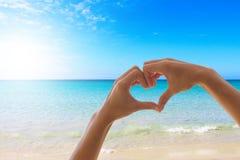 Die weiblichen Hände, die ein Herz machen, formen mit einem Hintergrundozean des blauen Himmels mit schönen Himmeln lizenzfreies stockfoto