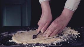Die weiblichen Hände, die Teig für Teigwaren durch Weinlese schneiden, rollen vorbei die schwarze Tabelle und pulverisieren durch stock video footage