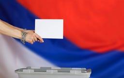 Die weiblichen Hände, die durch Metallkette befestigt wurden, warfen Stimmzettel im Ba Stockfoto