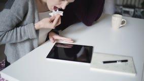 Die weiblichen Hände, die Oberflächenschirm abwischen, tablet PC mit dem Stoff, der auf Tabelle liegt stock video footage