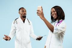 Die weiblichen und männlichen glücklichen afroen-amerikanisch Doktoren auf blauem Hintergrund lizenzfreies stockbild