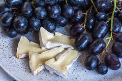 Die weiche Brie auf der Platte mit Trauben schließen oben Lizenzfreie Stockfotografie