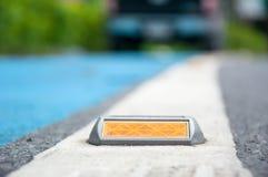 die Weichzeichnung des Reflektors oder des Bolzens auf Asphaltstraße Stockbilder