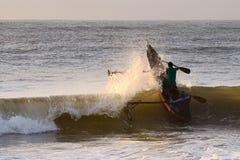 Die Welle brechen, gehendes am frühen Morgen fischen der Fischer Stockfotos