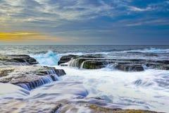 Die Welle fließt über verwitterte Felsen und Flusssteine bei Nord-Narrabeen Stockfotografie