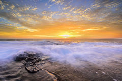 Die Welle fließt über verwitterte Felsen Stockfotografie