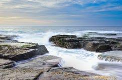 Die Welle fließt über verwitterte Felsen und Flusssteine bei Nord-Narrabeen Lizenzfreie Stockfotografie