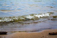 Die Welle hetzt auf dem sandigen Ufer Lizenzfreie Stockbilder