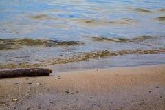 Die Welle hetzt auf dem sandigen Ufer Stockbild
