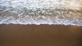 Die Welle schäumt auf dem sandigen Strand bei Sonnenuntergang Stockfoto