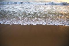Die Welle schäumt auf dem sandigen Strand bei Sonnenuntergang Stockbild