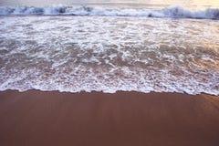 Die Welle schäumt auf dem sandigen Strand bei Sonnenuntergang Stockfotografie