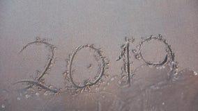 Die Welle wischt die Inschrift 2019 vom Sand ab Konzept des ausgehenden Jahres stock video